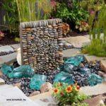 Lapos kavicsokkal díszített kőoszlop körülötte pedig üvegsziklák